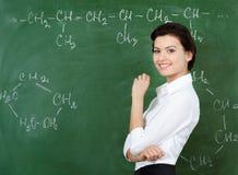突出在黑板的兴高采烈的教师 图库摄影