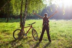 突出在晴朗的公园的兴奋女孩骑自行车者 图库摄影