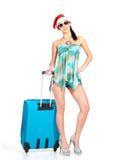 突出带着旅行手提箱的圣诞老人帽子的妇女 免版税库存图片