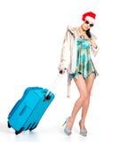 突出带着旅行手提箱的圣诞老人帽子的妇女 免版税库存照片