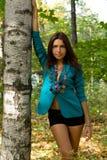 突出最近的桦树的美丽的女孩 免版税库存照片