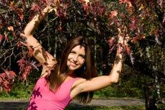 突出最近的秋天结构树的微笑的女孩 免版税库存照片