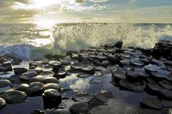 突出波浪的阳光碰撞在巨人堤道上六角玄武岩平板  免版税库存照片