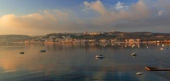 突出Mallieha海湾和Mallieha高度的金黄日出,反映在地中海水域 免版税库存图片