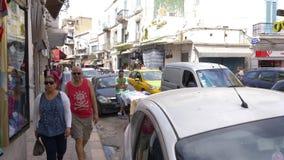 突尼斯,突尼斯- 2018年6月06日:走在城市街道上的阿拉伯人民在突尼斯 在狭窄的街道近的商店的汽车停车处 影视素材