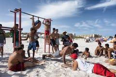 突尼斯:小组做健身的海滩的青年人 免版税库存照片