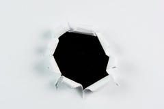 突破在白皮书的被撕毁的大黑洞 图库摄影