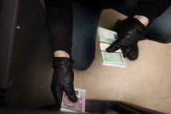 窃取从保险柜的窃贼金钱在犯罪现场 图库摄影