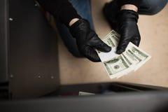 窃取从保险柜的窃贼金钱在犯罪现场 免版税库存照片