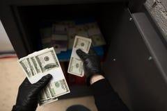 窃取从保险柜的窃贼金钱在犯罪现场 库存照片