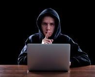 窃取信息的戴头巾计算机黑客 库存照片