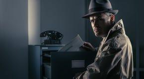 窃取文件的葡萄酒间谍在办公室 库存图片