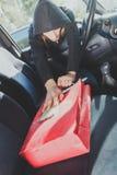 窃取智能手机和袋子从汽车的夜贼窃贼 库存照片