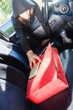 窃取智能手机和袋子从汽车的夜贼窃贼 免版税库存图片