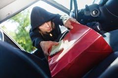 窃取智能手机和袋子从汽车的夜贼窃贼 库存图片