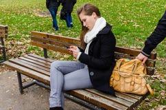 窃取袋子的扒手,当使用在公园长椅时的妇女电话 免版税库存图片