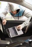 窃取从汽车的窃贼膝上型计算机 库存图片