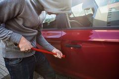 窃贼开头与撬杠的车门 免版税库存照片