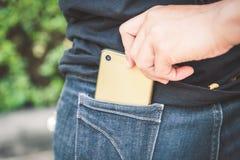 窃贼窃取从蓝色牛仔裤口袋的智能手机 免版税库存照片