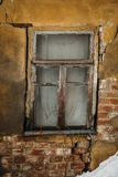 窗口在老沙沙响的被破坏的房子,在墙壁的镇压里 库存照片
