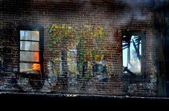 窗口战斗的火的消防员 免版税库存图片