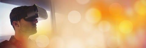 窗口的人与虚拟现实耳机橙色bokeh转折 库存图片