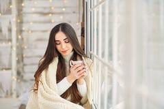 窗口的女孩与一个杯子在冬天 库存图片