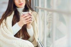 窗口的女孩与一个杯子在冬天 免版税库存照片