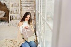 窗口的女孩与礼物在冬天 免版税库存照片