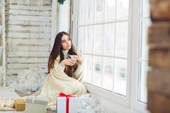 窗口的女孩与礼物在冬天 免版税库存图片