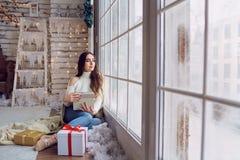 窗口的女孩与礼物在冬天 库存图片