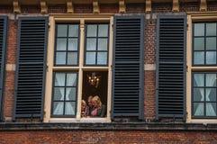 窗口的女孩在海牙的Binnenhof哥特式公共建筑 库存照片