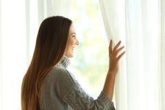 窗口的愉快的妇女开幕 免版税库存照片