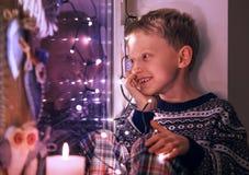 窗口的愉快的微笑的男孩与圣诞节装饰点燃 免版税库存照片