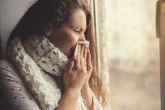 窗口的病的女孩与手帕 免版税库存照片