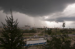 从窗口的看法在与黑暗的云彩和bustop的雨天 免版税库存图片