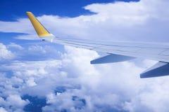 从窗口的看法,当在云彩的飞机飞行 免版税库存图片