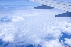 从窗口的看法,当在云彩的飞机飞行 免版税库存照片
