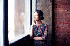 窗口的美丽的女孩 免版税库存照片