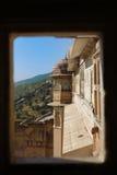 从窗口的观点在有绿色山的琥珀色的宫殿在背景 图库摄影