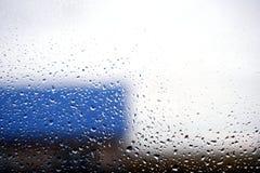 窗口结露和Defocused蓝色大厦 库存照片