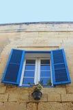 窗口:在砂岩房子的蓝色快门 免版税库存图片