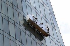 窗口洗涤的平台在摩天大楼的玻璃门面暂停了 免版税库存图片