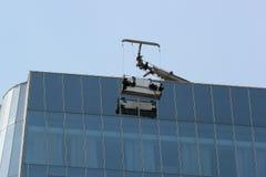 窗口洗涤的平台在摩天大楼的玻璃门面暂停了 库存图片