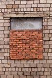 窗口bricked  窗口是被放置的砖 有窗口的灰色砖墙放置与红砖 窗口是半闭的 库存照片