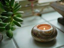 窗台的多汁植物与茶光蜡烛在阴沉的雨天 免版税库存照片