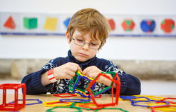建立与塑料块的小孩男孩几何图 库存图片