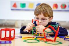 建立与塑料块的小孩男孩几何图 免版税库存图片