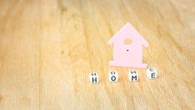 立方体信件的家庭词在丁香前面的上色了木表面上的房子标志 库存图片