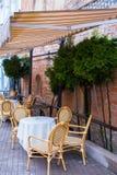 2017-06-25立陶宛、维尔纽斯、老城市空的咖啡大阳台、街道咖啡馆在维尔纽斯老市有桌的和椅子 免版税库存照片